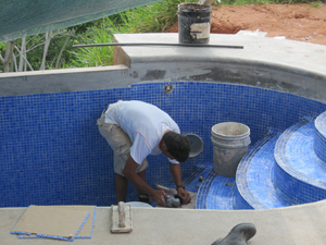 hand tiling a swimming pool